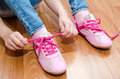 Child tying her shoes sitting on the floor at home closeup Royalty Free Stock Photo