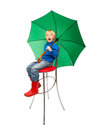 Child with umbrella boy green sitting on the chair Stock Photos