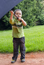 Child with umbrella in park an standing on a path a Stock Photo