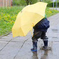 Child with umbrella in puddle a yellow jumping into a after the rain Stock Images