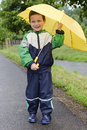 Child with umbrella in rain happy yellow Stock Images