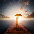 Child with umbrella standing alone wooden jetty in rain looking at the sea. Royalty Free Stock Photo
