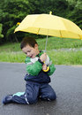 Child with umbrella yellow in the rain Royalty Free Stock Photos