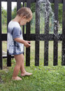 Child under garden water shower toddler playing with a tap on summer day Royalty Free Stock Photography