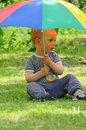 Child under umbrella little sitting a colorful in a garden Stock Photo