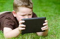 Child using tablet computer outdoors Royalty Free Stock Photography