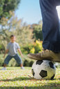 Child waiting for the football under fathers foot in park Royalty Free Stock Photo