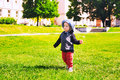 Child walking on meadow in the park at spring time. Royalty Free Stock Photo