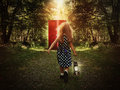 Child walking in woods to glowing red door a little is the holding a light and looking at a on the path for a mystery or Royalty Free Stock Photos