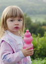 Child with water bottle in nature cute girl holding a pink plastic drinking while on a walk Stock Images