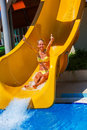 Child on water slide at aquapark show thumb up.