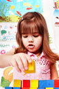 Child with wood block in preschool. Stock Image