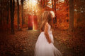 Child in woods looking at glowing red door a little is the wearing a white dress and a behind her on a wood path for a mystery or Royalty Free Stock Photos