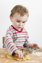Child working with dough on wooden desk young in vertical image looking at baking tools and Stock Photography