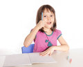 Child writing at desk gets an idea with pencils and notebook Royalty Free Stock Image