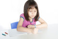 Child writing at desk with pencils and notebook Royalty Free Stock Image