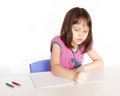 Child writing at desk with pencils and notebook Stock Photo