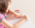 Child writing at desk with pencils and notebook Stock Photos