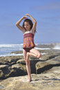 Child yoga pose young girl performs vrksasana tree on beautiful rocky beach in la jolla california Royalty Free Stock Photography