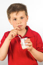 The child of yogurt photograph a eating over white background Stock Images