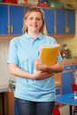 Childcare Worker Standing In Nursery Royalty Free Stock Photo