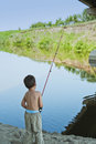 Childhood fishing addiction boy with spinning rod under a bridge catching fish Royalty Free Stock Image