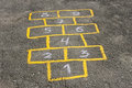 Childish game hopscotch on asphalt figures in painted with yellow paint Stock Photo