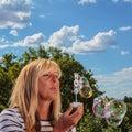 Childish mature woman blowing bubbles Stock Photo