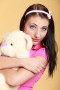Childish woman infantile girl hugging teddy bear portrait of young with headband holding toy in pink on orange longing for Royalty Free Stock Photo