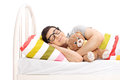 Childish young man sleeping with a teddy bear isolated on white background Royalty Free Stock Photography