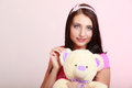 Childish young woman infantile girl in pink hugging teddy bear toy Stock Image