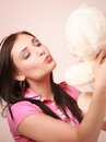Childish young woman infantile girl in pink kissing teddy bear toy portrait of with headband holding hugging on longing for Stock Images