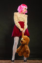 Childlike woman with dog toy on black mental disorder concept young wearing like puppet doll and big standing dark background Royalty Free Stock Image