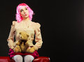 Childlike woman and teddy bear sitting on couch mental disorder concept young wearing like puppet doll with toy red dark black Stock Images