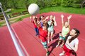 Children with arms up to ball play volleyball near the net on the court during sunny summer day outside Stock Image