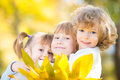 Children in autumn park happy with maple leaves Stock Photo