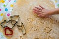 Children baking christmas cookies cutting pastry with a cookie cutter on a colorful table cloth Royalty Free Stock Photos