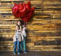 Children with balloons at wooden wall