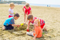 Children at the beach group of is playing digging sand Stock Images