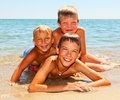 Children on a beach three kids enjoying summer day Stock Photography