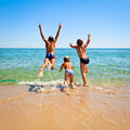 Children on a beach three kids jumping to the sea Royalty Free Stock Photography