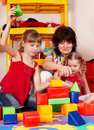 Children  with  block and woman in play room. Royalty Free Stock Image