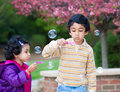 Children blowing bubbles in their yard spring Royalty Free Stock Photo