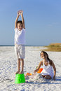 Children boy girl brother sister playing on beach happy having fun in the sand a with bucket and spade Royalty Free Stock Images
