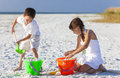 Children boy girl brother sister playing on beach happy having fun in the sand a with bucket and spade Royalty Free Stock Image