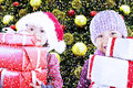 Children bring christmas gifts under tree Stock Images
