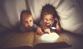 Children brother and sister read a book with aflashlight under b Royalty Free Stock Photo