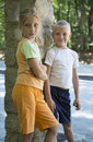Children brother and sister standing outdoors smiling beautiful blonde stand next to an outdoor column Stock Photos