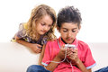 Children chat browsing internet cell phone kids girl and boy using smart for social media or listening music using earphones Royalty Free Stock Photo