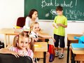 Children in classroom near blackboard with teacher Royalty Free Stock Image